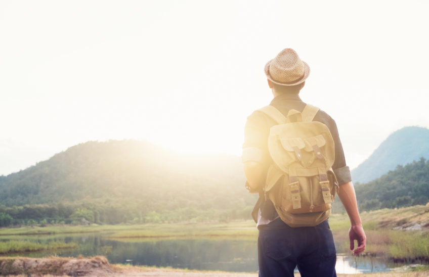 Young Man Traveler with backpack relaxing outdoor. Summer vacations and Lifestyle hiking concept. Retro filter effect, selective focus.